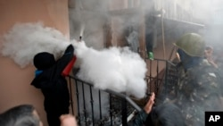 A pro-Russian protester fires a fire extinguisher at riot police inside at a police station building in Odessa, Ukraine, Sunday, May 4, 2014. Several prisoners that were detained during clashes that erupted Friday between pro-Russians and government suppo