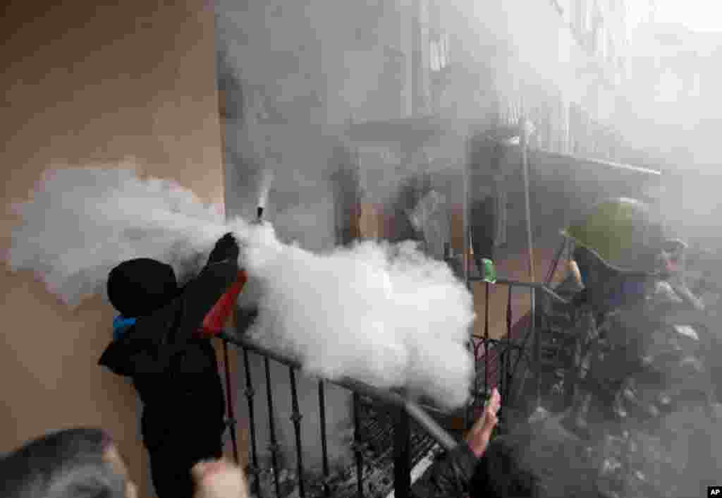 A pro-Russian protester shoots off a fire extinguisher aiming at riot police inside a police station in Odessa,  May 4, 2014.