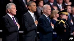 From left, outgoing Defense Secretary Chuck Hagel, President Barack Obama, Vice President Joe Biden and Joint Chiefs Chairman Gen. Martin Dempsey listen to the national anthem during a tribute to Hagel at Fort Myer in Arlington, Virginia., Jan. 28, 2015.