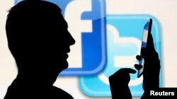 FILE - A man is silhouetted in front of a video screen with the Facebook and Twitter logos, in this picture illustration, Oct. 22, 2013.