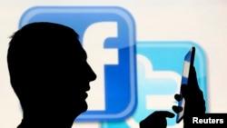 一名在脸书和推特的徽标前玩手机男子的侧影。(资料照片)
