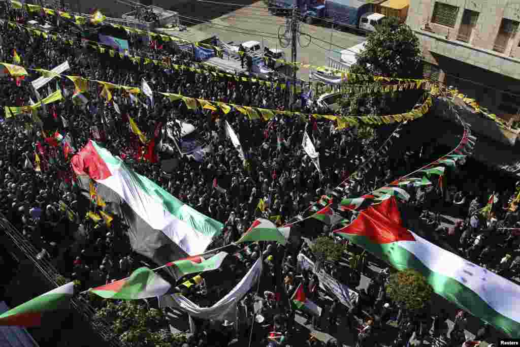 People carry large Palestinian flags during a rally to support the Palestinian U.N. bid for observer state status, Hebron,  occupied West Bank, November 29, 2012.