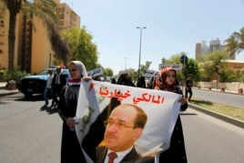 "Iraqis carry portraits of incumbent Iraqi Prime Minister Nuri al-Maliki as they gather in support of him in Baghdad August 13, 2014. Maliki said on Wednesday the appointment of Haider al-Abadi to replace him was a ""violation"" of the law."