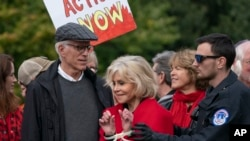 Actress and activist Jane Fonda, joined at left by actor Ted Danson, is arrested at the Capitol for blocking the street after she and other demonstrators called on Congress for action to address climate change, in Washington, Oct. 25, 2019.