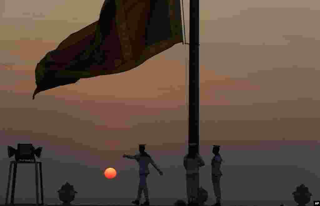 Navy sailors lower the Sri Lankan national flag as the sun sets on New Year's Eve in Colombo, Sri Lanka.