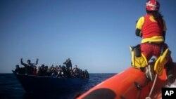 Des migrants sont aidés par des travailleurs humanitaires de l'ONG espagnole Open Arms, après avoir fui la Libye à bord d'une embarcation précaire en mer Méditerranée, à environ 110 miles au nord de la Libye, le 2 janvier 2021.