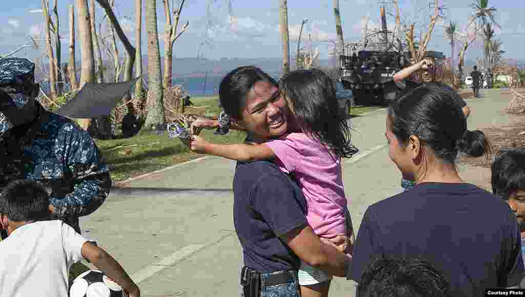 A member of the U.S. Navy hugs a child during a visit to Philippine Army base Camp Downes in support of Operation Damayan, Nov. 18, 2013. (U.S. Navy)