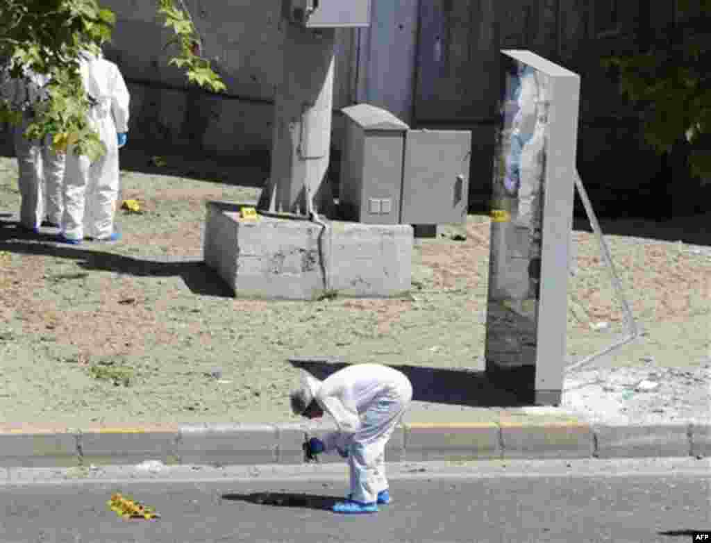 Forensic experts work at the scene after a bomb exploded at a bus stop during rush hour in Istanbul, Turkey, Thursday, May 26, 2011. A bomb placed on a bicycle near a bus stop exploded during morning rush hour in Istanbul on Thursday, injuring seven peop