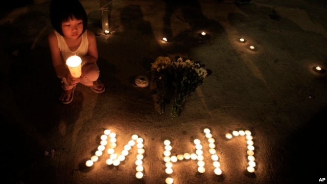 FILE - A girl holding a candle squats next to candles forming the letters MH17 during an event to mourn the victims of the crashed Malaysia Airlines Flight 17, in Kuala Lumpur, Malaysia, July 20, 2014.