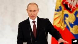 Tổng thống Nga Vladimir Putin phát biểu trước Quốc hội Nga, lên án các nhà lãnh đạo Kyiv đã thay thế ông Yanukovych, và nói rằng họ đã vi phạm quyền của người sắc tộc Nga ở Crimea, ngày 18/3/2014.
