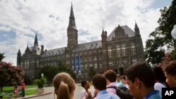 FILE - Prospective students tour Georgetown University's campus in Washington, D.C., July 10, 2013.