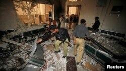 Petugas keamanan tengah memeriksa lokasi ledakan bom di Kompleks Pengadilan di Peshawar, Pakistan (18/3).