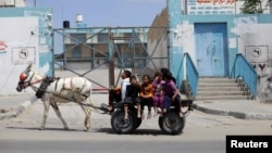 Palestinian children ride a donkey cart past a U.N. food distribution center in Khan Younis refugee camp, southern Gaza Strip, April 5, 2013.