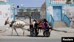 Palestinian children ride a donkey cart past a U.N. food distribution center in Khan Younis refugee camp, southern Gaza Strip, April 5, 2013.