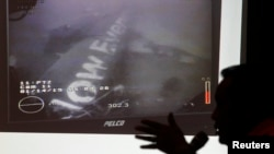 Head of the National Search and Rescue Agency Fransiskus Bambang Soelistyo is seen with an image believed to be of the fuselage of AirAsia Flight QZ8501, taken by an underwater ROV provided by the Singaporean Navy, during a news conference in Jakarta, Jan. 14, 2015.