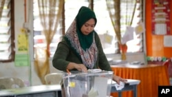 FILE-A woman casts her vote during the by-election at a polling station in the southern coastal town of Port Dickson.