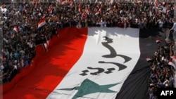 Người biểu tình ủng hộ Tổng thống Syria mang theo một lá cờ khổng lồ Syria trong cuộc biểu tình chống lại quyết định của Liên đoàn Ả Rập tại Damascus, ngày 13/11/2011