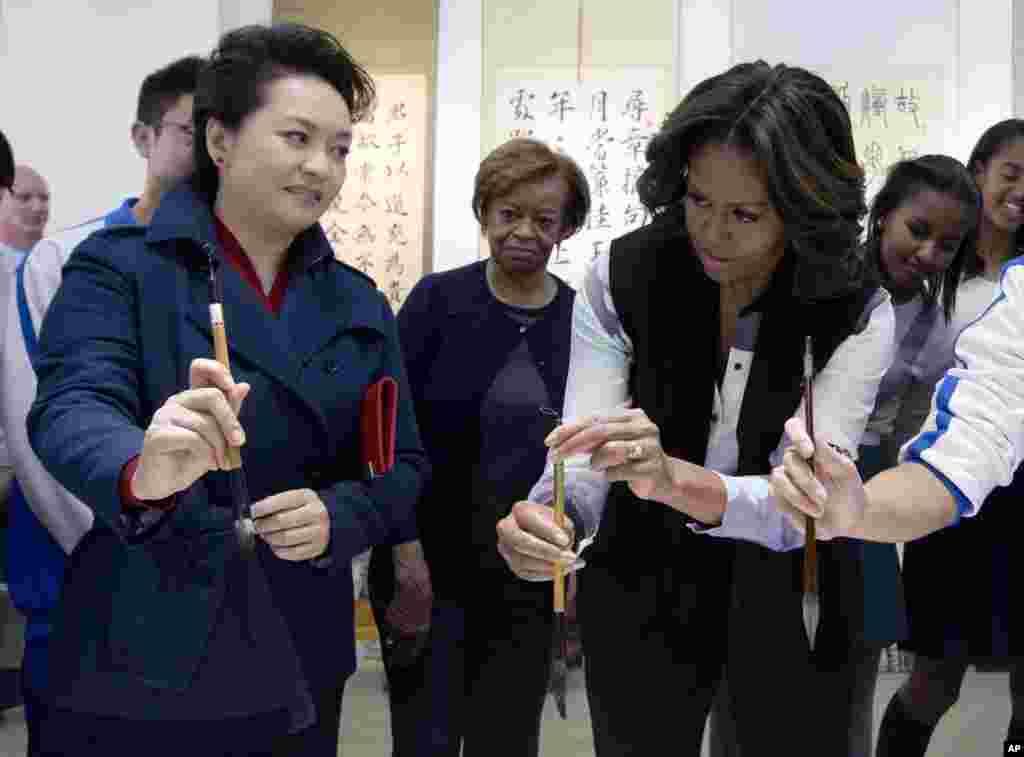 中国国家主席习近平的夫人彭丽媛3月21日向美国第一夫人米歇尔.奥巴马展示如何使用毛笔,当时她们在参观北京一所学校的中国书法课。