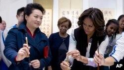 在参观书法课时,习近平夫人彭丽媛教美国第一夫人米歇尔·奥巴马怎样用毛笔写字