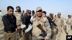 Pasukan paramiliter Pakistan membawa mayat seorang militan yang tewas dalam serangan di Quetta, Pakistan, Jumat, 15 Agustus 2014.