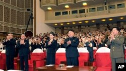 In this photo released by the Korean Central News Agency (KCNA) and distributed in Tokyo by the Korea News Service on Monday, July 9, 2012, North Korean leader Kim Jong Un, center right, and others clap as they watch performance by North Korea's new Moran