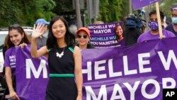 FILE - Boston mayoral candidate Michelle Wu waves while walking in the Roxbury Unity Parade, in Boston's Roxbury neighborhood, July 18, 2021.