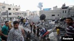Khói bốc lên từ các tòa nhà sau một vụ không kích từ Israel, theo lời các nhân chứng, trong khi người dân Palestine tìm kiếm các nạn nhân nằm dưới đống đổ nát của một ngôi nhà.