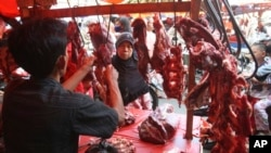 A woman buys meat at a market in Jakarta, Indonesia, Friday, Aug. 17, 2012. Today, a kilogram of beef can cost more than $13.