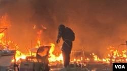 理工大學校園一個出入口位置星期一下午突然起火,並且發出多次爆炸聲,濃煙四起,一名留守者上前用水喉救火。(攝影: 美國之音湯惠芸)