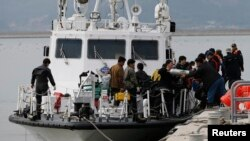FILE - Divers return after a search and rescue operation for a South Korean ferry that sank in 2014. The South Korean Coast Guard is attempting to rescue nearly 200 people from a ferry that hit a rock off the southwest coast.
