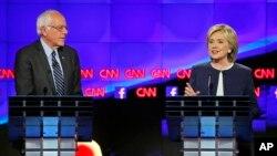 13일 밤 미국 서부 라스베가스에서 열린 민주당 대선 예비후보 TV 토론회에서 버니 샌더스 상원의원(왼쪽)이 힐러리 클린턴 전 국무장관의 발언을 듣고 있다.