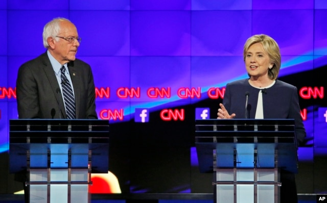 FILE - Former Secretary of State Hillary Clinton talks as Sen. Bernie Sanders of Vermont listens during the CNN Democratic presidential debate in Las Vegas, Oct. 13, 2015. The two hold another debate Sunday in Flint, Mich.