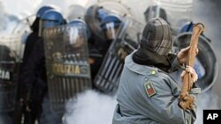 A demonstrator wearing a stolen Guardia di Finanza jacket throws a metal pole at the Guardia di Finanza during anti-government clashes near the parliament in Rome, 14 Dec 2010.