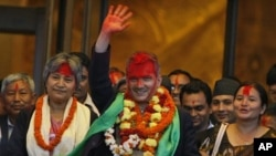 Communist Party of Nepal (Maoist) leader Baburam Bhattarai, center, with his face smeared with vermilion by supporting lawmakers, waves as he comes out of the parliament building after being elected as new prime minister in Katmandu, Nepal, August 28, 201