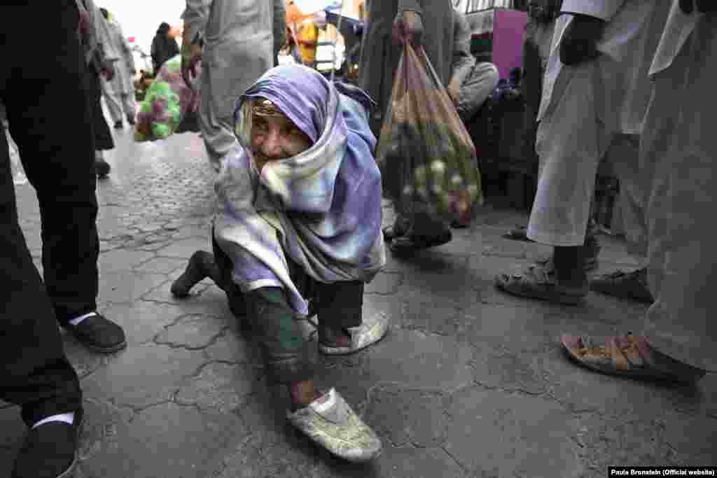 مهتاب ۷۰ ساله در حال گدایی در یک جاده ای مزدحم شهر کابل. او مجبور شده خود را طور جلوه دهد که معلول است تا رهگزاران به حال اش رحم کنند و مقدار پولی برایش بدهند. او می گوید برای بقای حیات اش مجبور است خود را این گونه جلوه دهد چرا که در شهر شمار گدا ها و افراد محتاج زیاد است. شوهرش در زمان طالبان کشته شده و چهار فرزند دارد. مهتاب سواد ندارد و بیکار است.