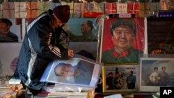 在中共领袖毛泽东冥诞120周年之际,一名旧书贩在北京某旧货市场摆放毛泽东画像。