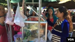 Garment workers buy food during a lunch break on national road #2 in Meanchey district, Phnom Penh, Cambodia. (Photo: Phorn Bopha/VOA Khmer)