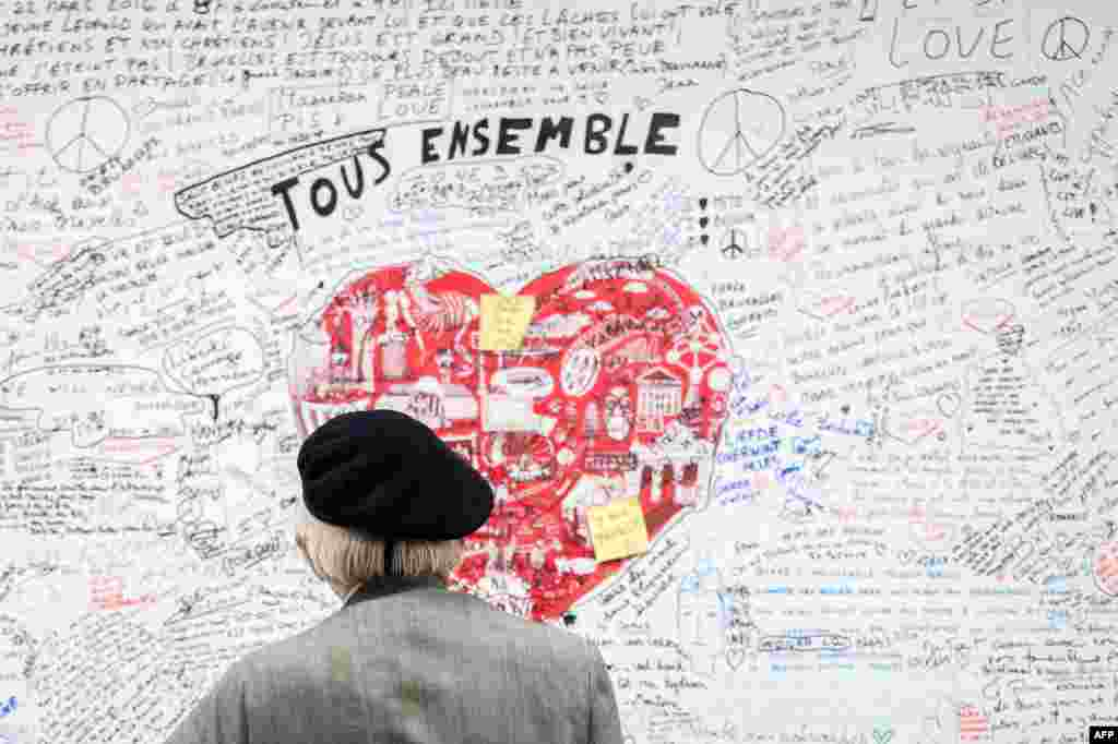 A man looks at a memorial panel for the victims of the March 22 attacks at the entrance of the Maelbeek-Maalbeek subway station in Brussels, Belgium.