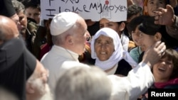 FILE - Pope Francis greets migrants and refugees at Moria refugee camp near the port of Mytilene, on the Greek island of Lesbos, April 16, 2016.