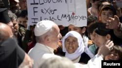 Paus Fransiskus menyalami para migran dan pengungsi di kamp penampungan pengungsi dekat pelabuhan Mytilene, Lesbos, Yunani (16/4).