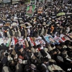 Anti-government protestors pray around the bodies of the demonstrators who were killed on Friday's clashes with Yemeni security forces, during their funeral procession in Sanaa,Yemen, March 20, 2011