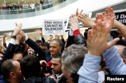 FILE - Zaman editor-in-chief Ekrem Dumanli, escorted by plainclothes police officers, is cheered on by his colleagues as he leaves the headquarters of Zaman daily newspaper in Istanbul, Dec. 14, 2014. Turkish police had raided media outlets close to U.S.-based Muslim cleric Fethullah Gulen and detained 23 people nationwide in operations against what President Tayyip Erdogan said was a network conspiring to topple him.