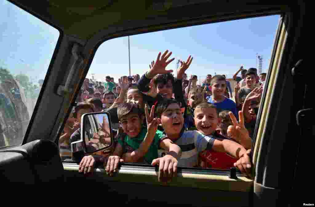 이라크 키르쿠크 지역에서 어린이들이 정부군 차량 행렬을 반기고 있다.