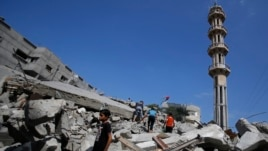 Palestinians stand in rubble of the al-Qassam mosque in Nuseirat refugee camp, central Gaza Strip, after it was hit by an Israeli airstrike, Saturday, Aug. 9, 2014.
