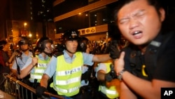 A pro-democracy protester is struck by a baton as riot police move on an occupied section of a roadway in the Mong Kok district of Hong Kong, Oct. 18, 2014.