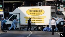 Petrugas forensik memindahkan mobil van di Finsbury Park, utata London, di mana sebuah kendaraan menabrak pejalan kaki di London utara, 19 Juni 2017. (AP Photo/Frank Augstein).