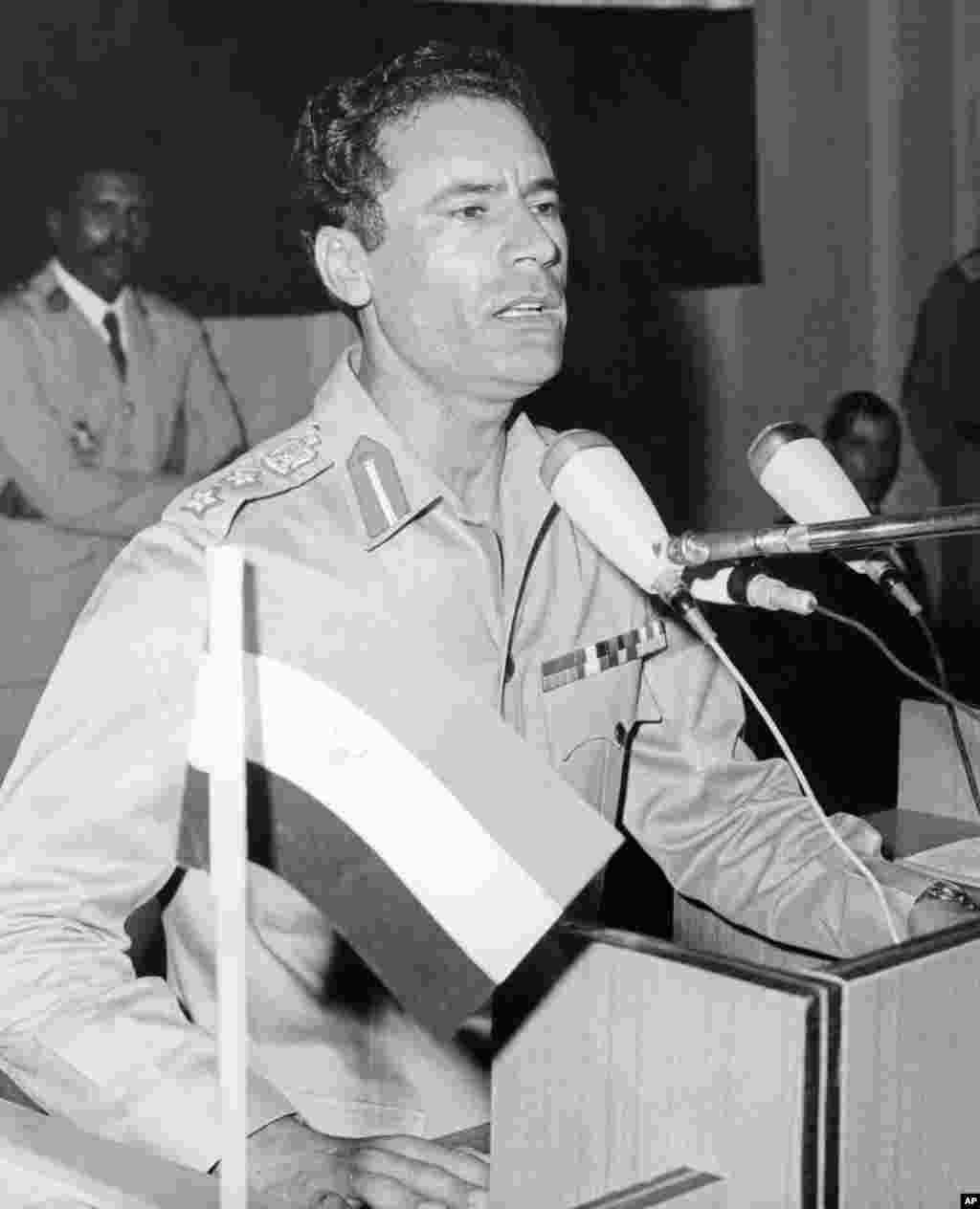 """利比亚国家元首卡扎菲上校生于1942年,1963年组建被称作""""自由军官运动""""的革命军官组织。该组织于1969年9月1日推翻了利比亚国王伊德国里斯一世(Idris),并以""""自由、社会主义和团结的""""名义宣布成立了""""大阿拉伯利比亚人民社会主义民众国""""。(法新社)"""
