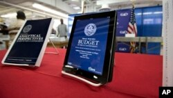 President Obama's proposed budget plan for fiscal year 2014, displayed in digital format, right, at the U.S. Government Printing Office, Washington, April 8, 2013.