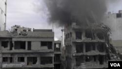 ຄວັນໄຟກໍາລັງພຸ່ງຂື້ນຈາກຕຶກ ທີ່ນັກເຄຶ່ອນໄຫວ ກ່າວວ່າຖືກ ໂຈມຕີຈາກ ພວກຈົງຮັກພັກດີ ຕໍ່ປະທານາທິບໍດີ Bashar al-Assad.