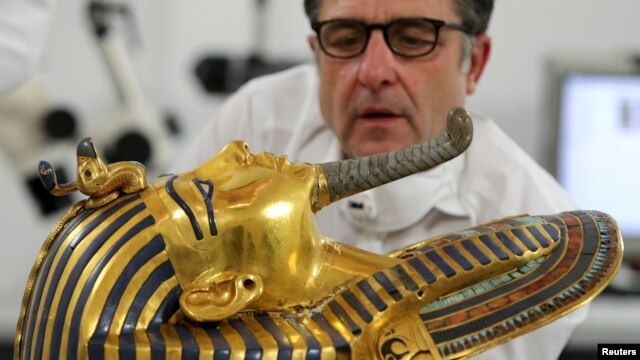 German conservator Christian Eckmann works on the restoration of the golden mask of King Tutankhamun at the Egyptian Museum in Cairo, Egypt, Oct. 20, 2015.